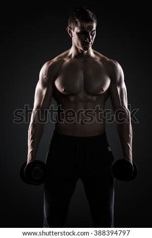 Muscular man showing perfect body with dumbbells on black background #388394797