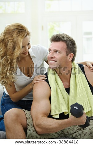 Muscular man sitting on sofa at home, doing excercise with hand barbell, her girlfriend embracing from behind.
