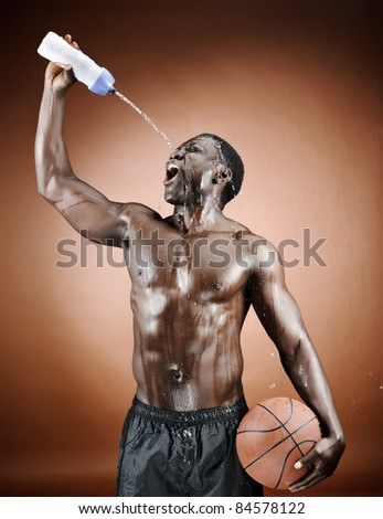 Muscular man spraying himself with water after his intense workout