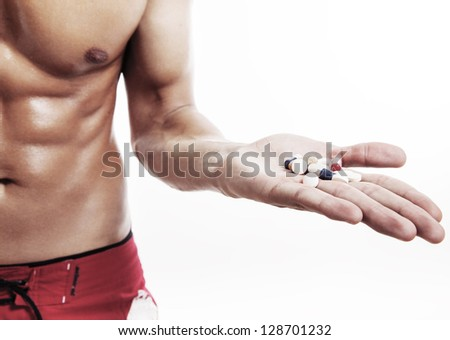 muscular man torso with hand full of pills on white