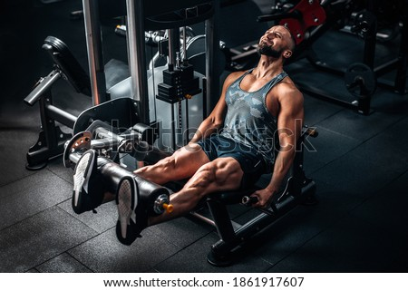 Muscular man using weights machine for legs at the gym. Hard training Foto stock ©