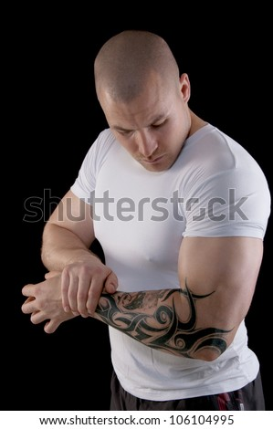Muscular man with a tattoo on his arm flexing his biceps