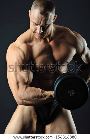 Muscular man with dumbbell in studio showing his strong biceps