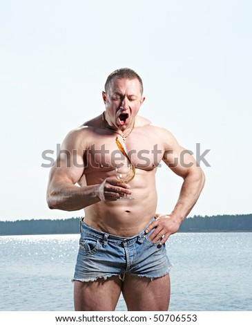 Muscular man with glass of red drink at  lake on sunny day splashing drink