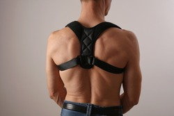 Muscular man with posture corrector. Scoliosis, Kyphosis treatment