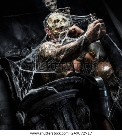 Muscular man with skull on his face and sword in his hand posing on the throne in spiders web on gray background.