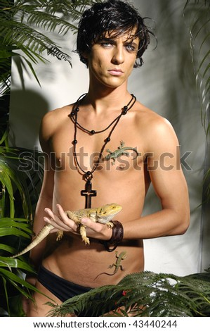 muscular man with snake in tropical green forest