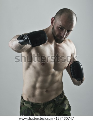 Muscular man with the gloves striking a punch.