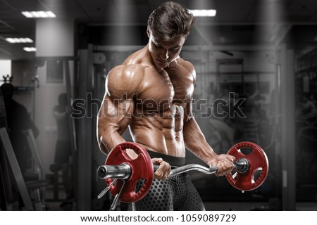 Muscular man working out in gym doing exercises, strong bodybuilder, abs