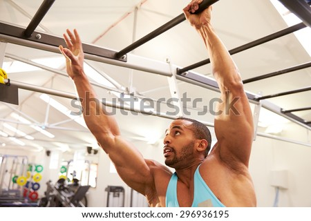 Muscular man working out on monkey bars at a gym