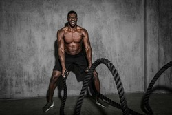 Muscular man working out on the battle ropes in a gym
