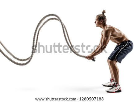 Muscular man working out with heavy ropes. Photo of sporty male with naked torso isolated on white background. Strength and motivation. Side view. Full length