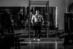Muscular man workout with barbell at gym. Bodybuilder athletic man with six pack, perfect abs, shoulders, biceps, triceps, chest. Barbells workout. Black and white.