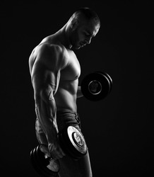 Muscular men bodybuilder is working out in gym, lifting alternately two dumbbells, doing exercises for biceps and looking down over black background. Young man lifting weights. Black and white