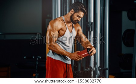 Muscular Men Drinks Protein Drink, Energy Drink in the Gym