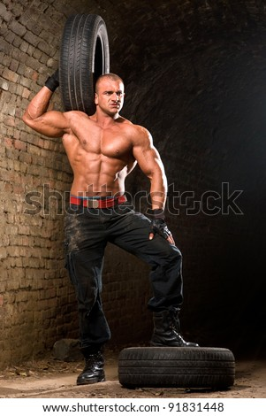 Muscular men holding tire on his shoulder