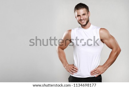 Muscular model man in white t-shirt on a gray background. Sporty guy showing his big shoulders,biceps, triceps. Workout, bodybuilding, Shirt design, people concept. Mock up template for design print.