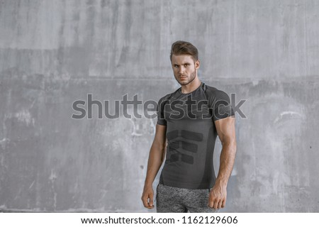 Muscular model sports young man in fashion sportswear on urban gray background. Portrait of brutal sporty  strong muscle guy with a modern trendy hairstyle. Sport, workout, healthy, lifestyle concept.