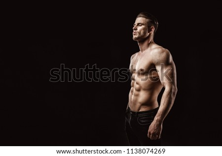 Muscular model sports young man on dark background. Fashion portrait of  strong brutal guy with a modern trendy hairstyle. Sexy torso. Male flexing his muscles. Sport workout bodybuilding concep.
