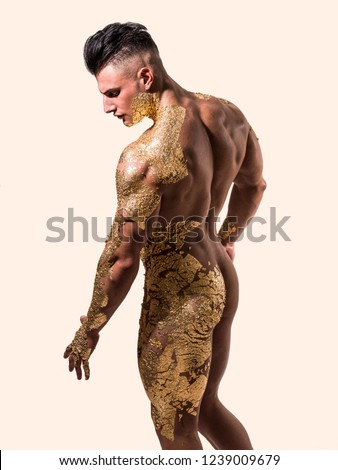 Muscular naked man covered with golden film looking down sensually on light background