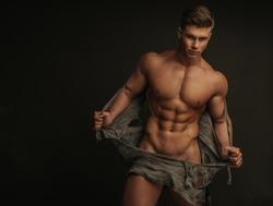 Muscular naked man tearing off his shirt
