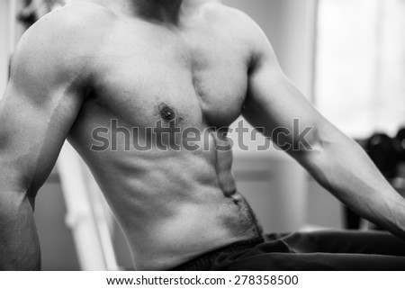 Muscular power athletic male bodybuilder upper body in fitness center. Back and white photo