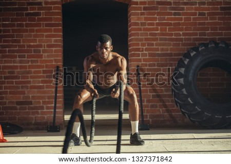 Muscular powerful determined african man training with rope in functional training in outdoor gym with brick walls, strengthen the muscles of the shoulders, which is important for boxers and swimmers #1327371842