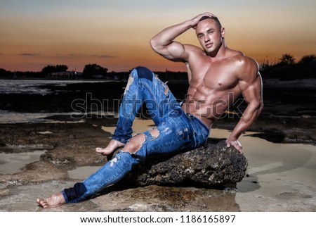 Muscular sexy guy in blue jeans posing sitting on a rock in the sea at sunset