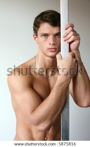 Muscular sexy man leaning on a metal pole