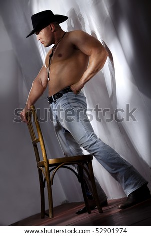 Muscular shirtless cowboy leaning on chair against a white wall ...