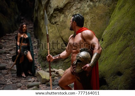 Muscular Spartan warrior with stunning ripped strong body walking away from his wife looking at her with love goodbye relationships love people medieval couples romance affectionate. #777164011