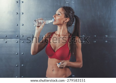 Muscular sporty athlete woman drinking water at the gym after exercising working out fitness, sport, training and lifestyle concept
