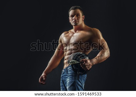 Muscular sporty man with helmet. Sportsmen in black background. Ab and biceps
