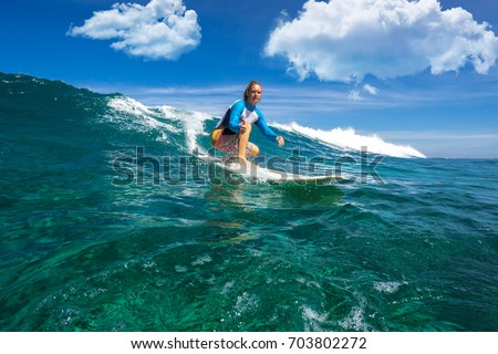 muscular surfer with long white hair riding on big waves on the Indian Ocean island of Mauritius