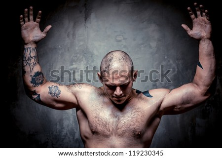 Muscular tattooed man with hands raised up posing over grey background