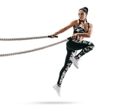 Muscular woman jumping with heavy ropes. Photo of latin woman in military sportswear isolated on white background. Strength and motivation.