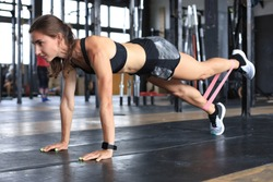 Muscular woman on a plank position use fitness gum.