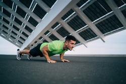 Muscular young ethnic man in activewear performing push ups during training on concrete pavement on stadium while getting ready for competition