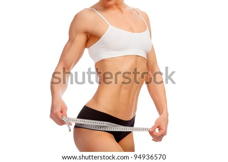 Muscular young girl measuring her thighs with tape