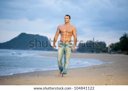 Muscular young male walking along a beach