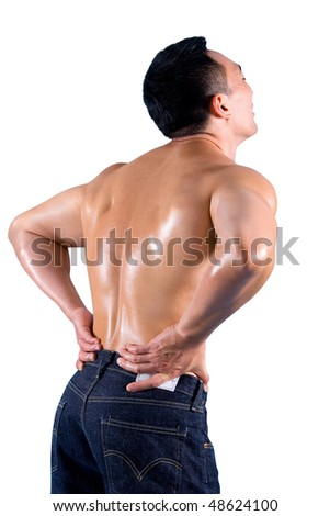 Muscular young man clutching his lower back, suffering from back pain.