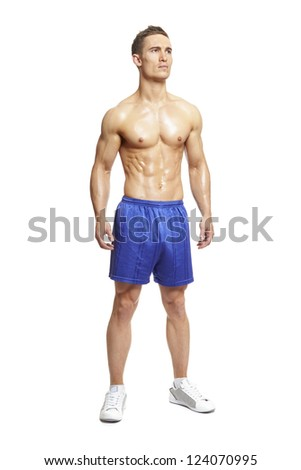 Muscular young man flexing muscles in sports outfit on white background