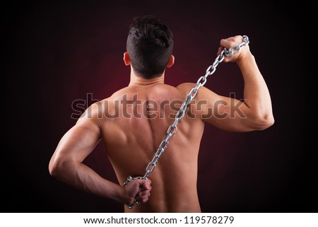 Muscular young man from back on black background