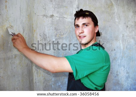 Muscular young man in a builder uniform.