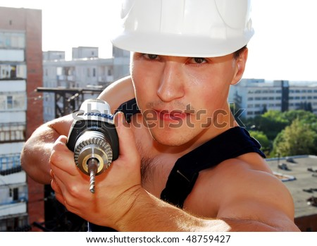 Muscular young man in a builder uniform. - stock photo