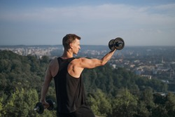 Muscular young man in activewear training arms with dumbbells outdoors. Caucasian male athlete having active workout on fresh air. Motivation concept.