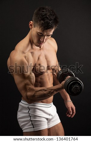 Muscular young man lifting a dumbbell over black background