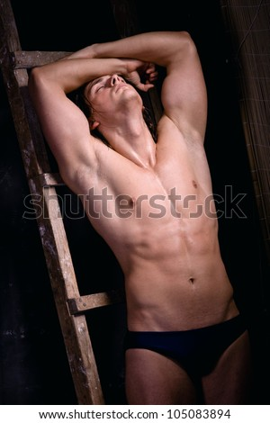Muscular young man on black background near the staircase