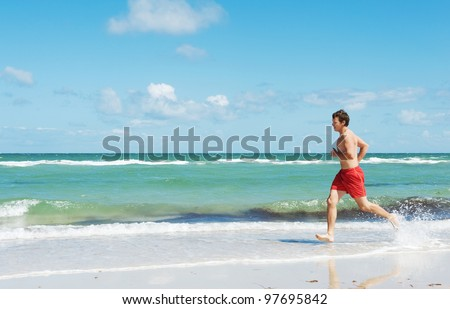 muscular young man running along the coast