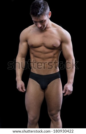 Muscular young man semi naked in bathing suit looking down, isolated on black - stock photo
